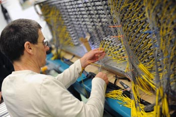 Technicians work on the 3,400 sensors to optical cables on the detector